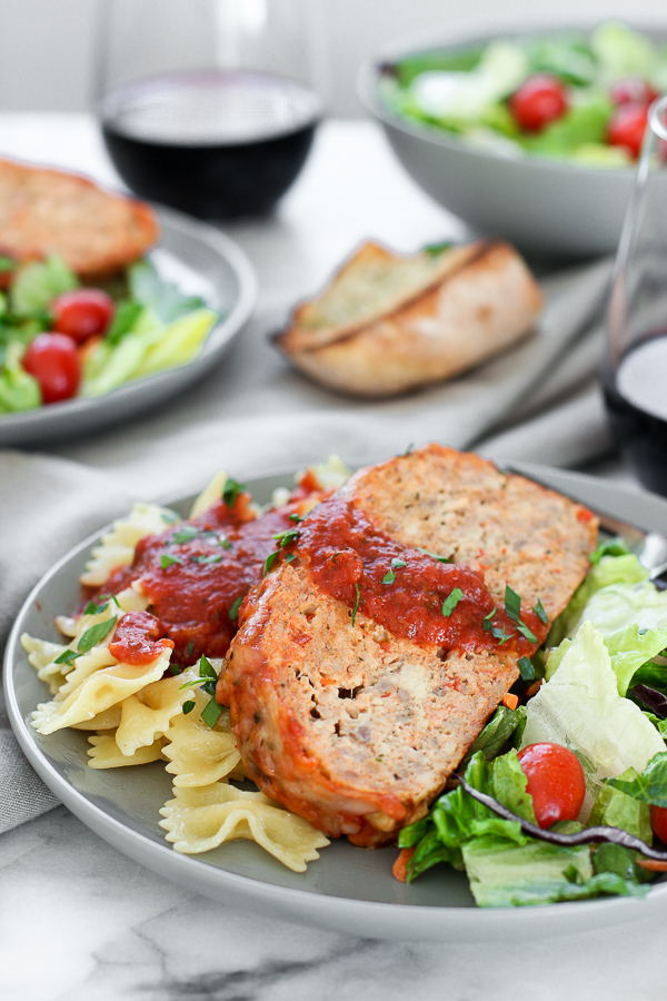 Vertical shop of Italian turkey meatloaf plated with pasta, salad and wine