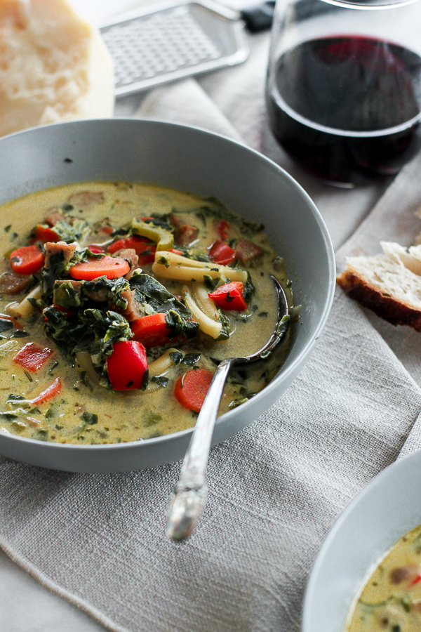 Photo of Creamy Italian Chicken Sausage Soup in the bowl with bread and wine.